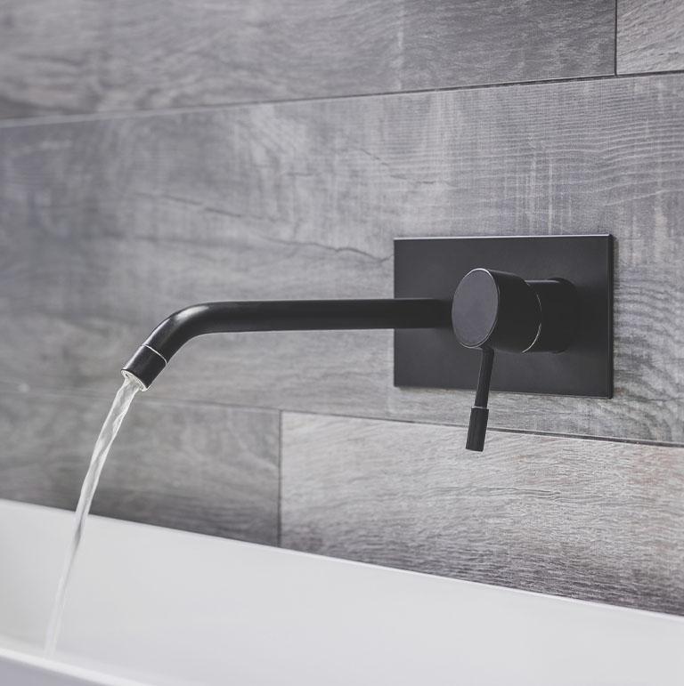 woda lecąca z baterii łazienkowej zamontowanej w ścianie